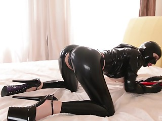 Lucy Latex masturbates by oneself using her hand and a big red dildo